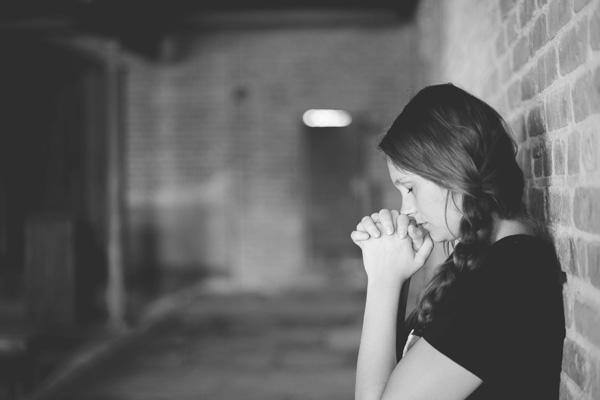woman praying alone in corridor