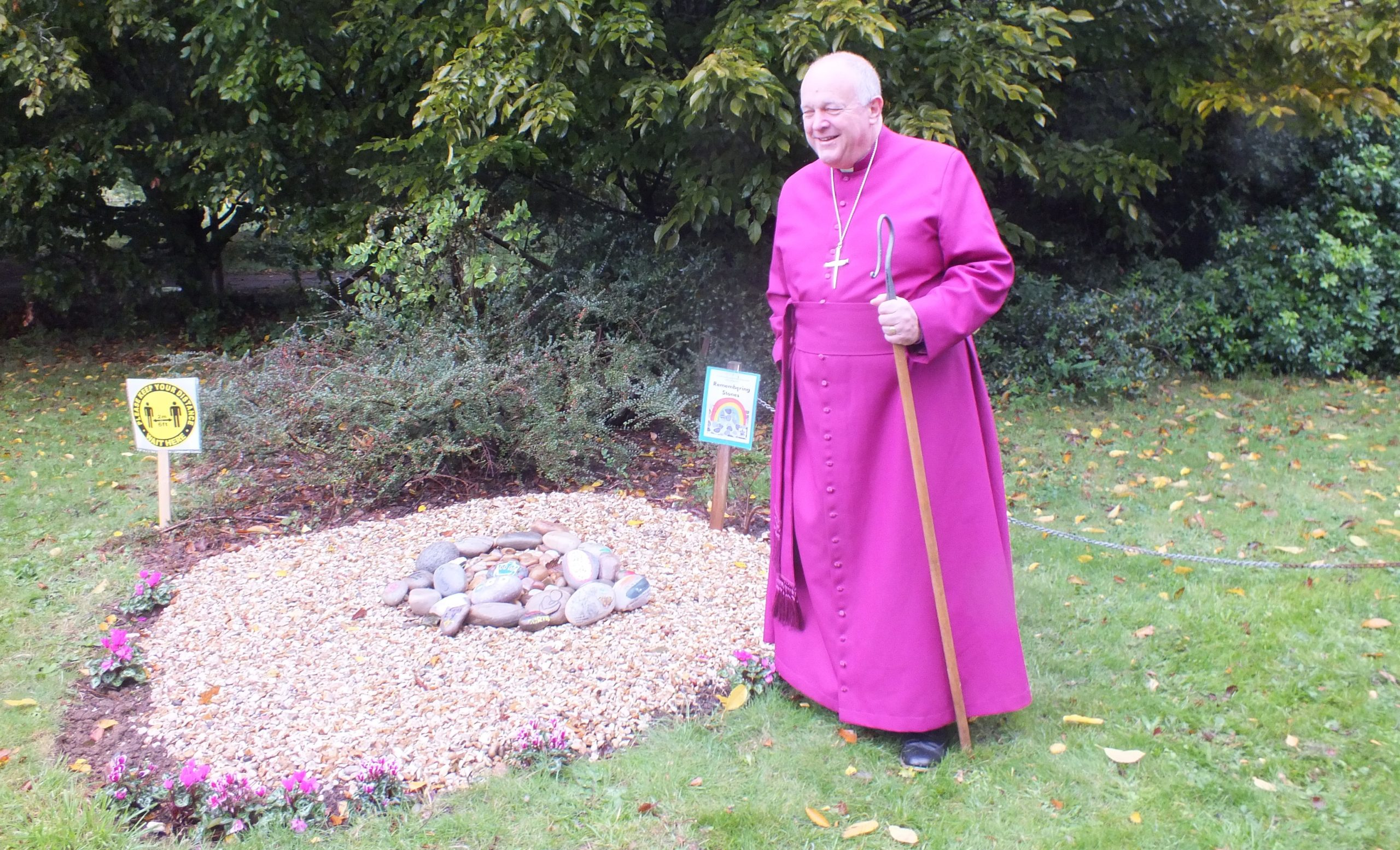 Bishop standing by cairn