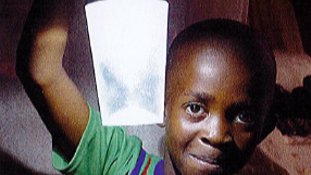 young boy holding up solar light