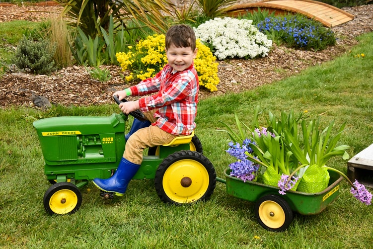 Child on small tractor and trailer