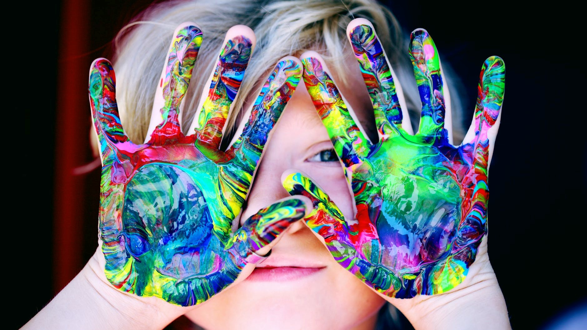 child with brightly painted hands
